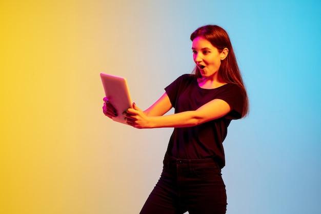 네온 불빛에 그라데이션 파란색 노란색 스튜디오 배경에 젊은 백인 여자의 초상화. 청소년, 인간의 감정, 표정, 판매, 광고의 개념. 아름다운 갈색 머리 모델.