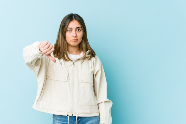 Young caucasian woman showing a dislike gesture, thumbs down. disagreement concept.