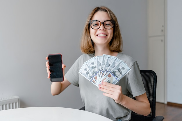Young caucasian woman showing money and mobile app sitting in the apartment