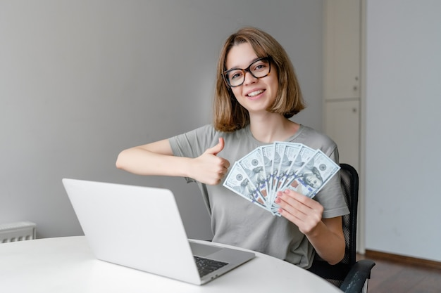 Young caucasian woman showing money and thumb up sitting with laptop at home