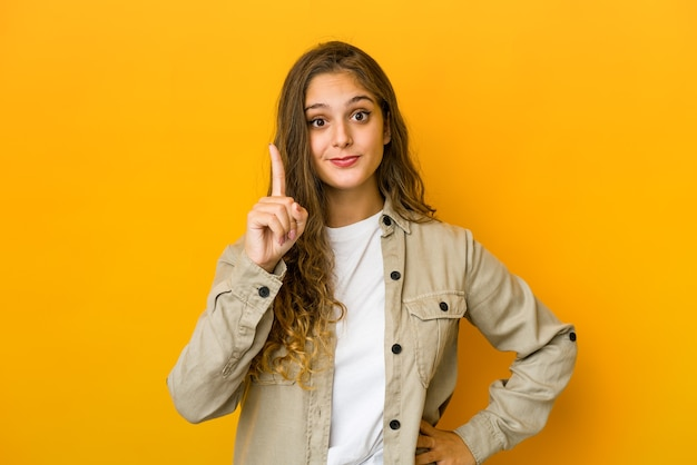 Young caucasian woman showing number one with finger.