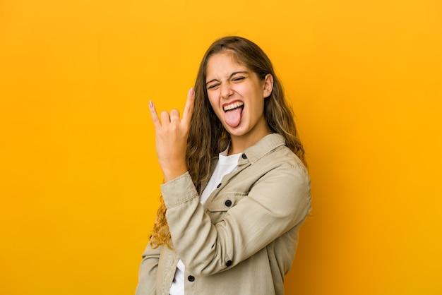 指でロックジェスチャーを示す若い白人女性