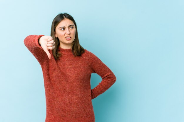 Young caucasian woman showing thumb down and expressing dislike.