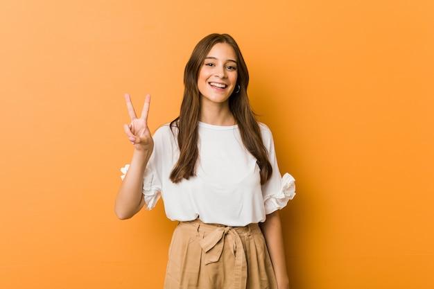 勝利のサインを示し、広く笑っている若い白人女性。 Premium写真