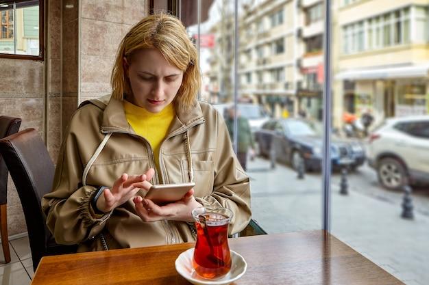 若い白人女性は、彼女の前にトルコのお茶を片手にカフェの窓際のテーブルに座って、スマートフォンの画面で情報を表示します。