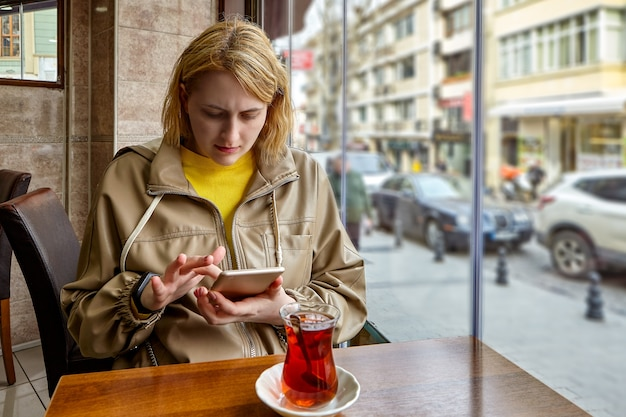 Young caucasian woman sits at table by window in cafe with turkish glass of tea in front of her and views information on smartphone screen.
