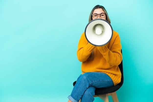 Молодая кавказская женщина сидит на стуле и кричит в мегафон