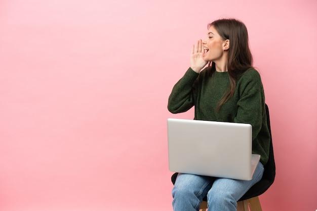 Молодая кавказская женщина сидит на стуле со своим ноутбуком и кричит с широко открытым ртом