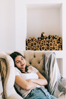 Young caucasian woman sitting on armchair in living room sleeping after hard-working day, take nap or daydream