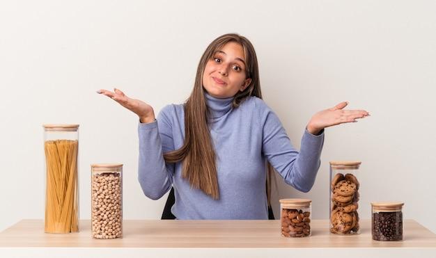 흰색 배경에 격리된 음식 냄비가 있는 테이블에 앉아 있는 젊은 백인 여성은 의심을 품고 어깨를 으쓱하며 몸짓을 합니다.