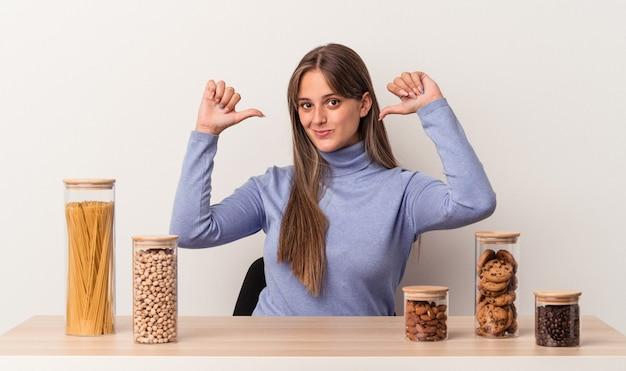 흰색 배경에 격리된 음식 냄비가 있는 테이블에 앉아 있는 젊은 백인 여성은 따라야 할 본보기인 자부심과 자신감을 느낍니다.