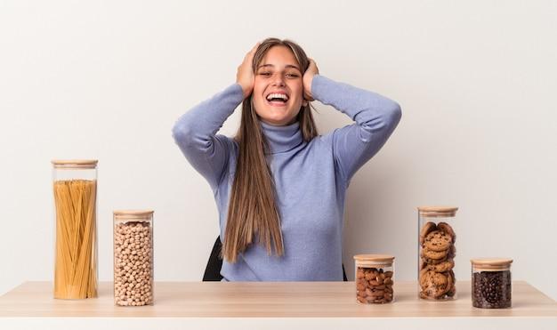 白い背景で隔離のフードポットとテーブルに座っている若い白人女性は、頭に手を置いて喜んで笑います。幸福の概念。