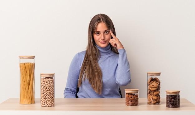 흰색 배경에 격리된 음식 냄비가 있는 테이블에 앉아 있는 젊은 백인 여성은 손가락으로 사원을 가리키며 생각하고 작업에 집중했습니다.