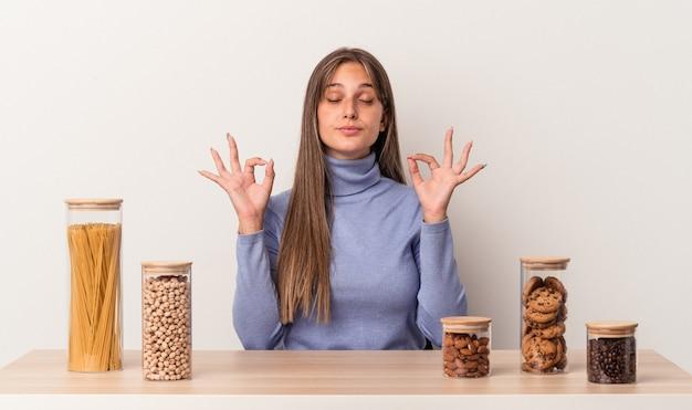 흰색 배경에 격리된 음식 냄비가 있는 테이블에 앉아 있는 젊은 백인 여성은 힘든 하루를 보낸 후 긴장을 풀고 요가를 하고 있습니다.