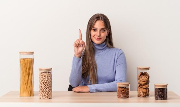 指でナンバーワンを示す白い背景で隔離のフードポットとテーブルに座っている若い白人女性。