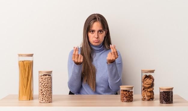 그녀는 돈이 없음을 보여주는 흰색 배경에 고립 된 음식 냄비와 함께 테이블에 앉아 젊은 백인 여자.