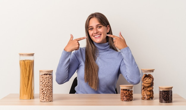 흰색 배경에 격리된 음식 냄비가 있는 테이블에 앉아 있는 젊은 백인 여성은 손가락을 입으로 가리키며 미소를 짓고 있습니다.