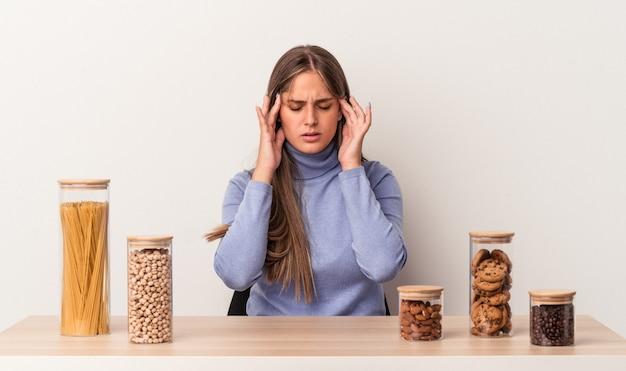 寺院に触れて頭痛を持っている白い背景で隔離のフードポットとテーブルに座っている若い白人女性。