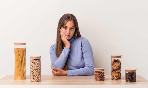 흰색 배경에 격리된 음식 냄비가 있는 테이블에 앉아 있는 젊은 백인 여성은 지루하고 피곤하며 편안한 하루가 필요합니다.