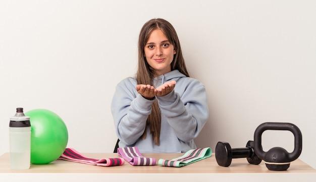手のひらで何かを保持し、カメラに提供する白い背景で隔離のスポーツ用品とテーブルに座っている若い白人女性。