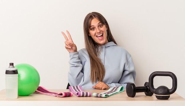 白い背景に隔離されたスポーツ用品とテーブルに座っている若い白人女性は、指で平和のシンボルを喜んで気楽に示しています。