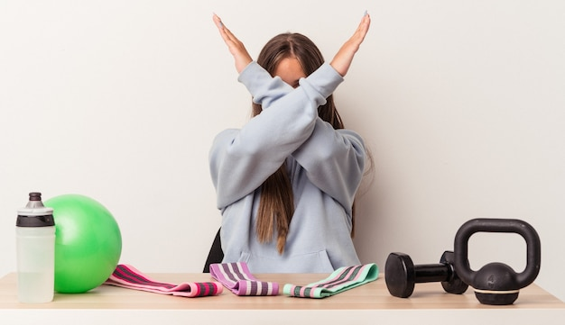 2つの腕を交差させたまま、白い背景で隔離のスポーツ用品とテーブルに座っている若い白人女性、否定の概念。