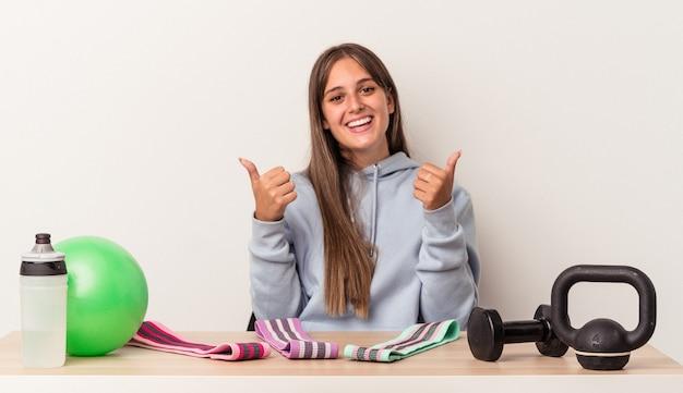 Молодая кавказская женщина, сидящая за столом со спортивным оборудованием, изолированным на белом фоне, поднимает большие пальцы руки вверх, улыбается и уверенно.