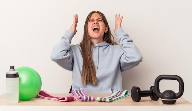 空に向かって叫んで、見上げて、イライラして、白い背景で隔離のスポーツ用品とテーブルに座っている若い白人女性。