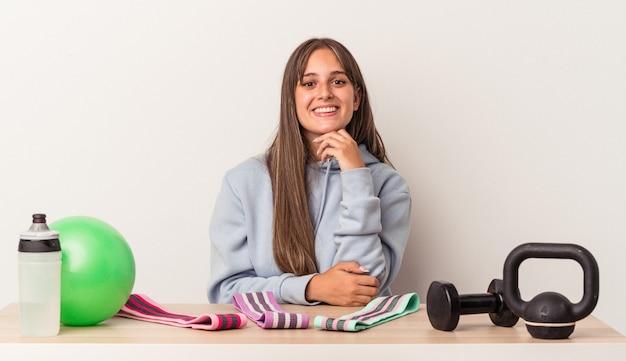 白い背景で隔離のスポーツ用品とテーブルに座って幸せと自信を持って笑顔、手で顎に触れている若い白人女性。