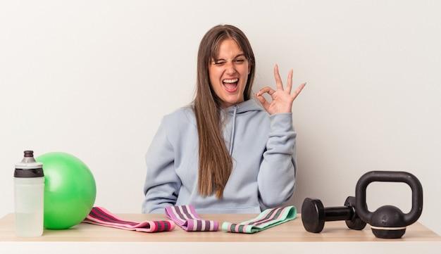 白い背景で隔離のスポーツ用品とテーブルに座っている若い白人女性は目をまばたきし、手で大丈夫なジェスチャーを保持します。