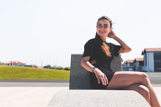 Young caucasian woman sitting at a bench