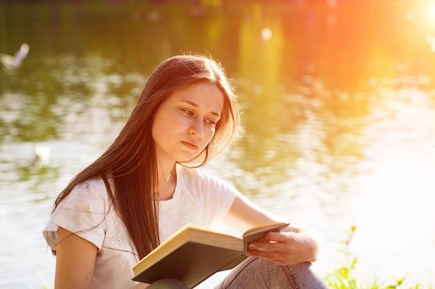 本を読んで、晴れた夏の日、公園の湖のほとりに座っている若い白人女性