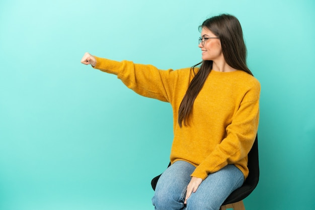 Young caucasian woman sitting on a chair isolated on blue background giving a thumbs up gesture