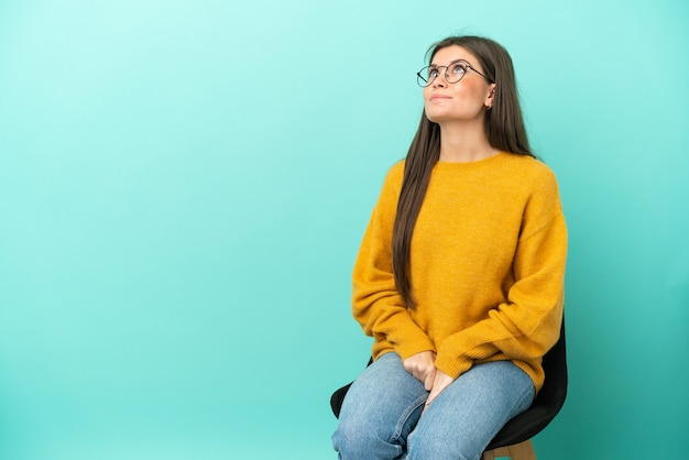 Young caucasian woman sitting on a chair isolated on blue background and looking up