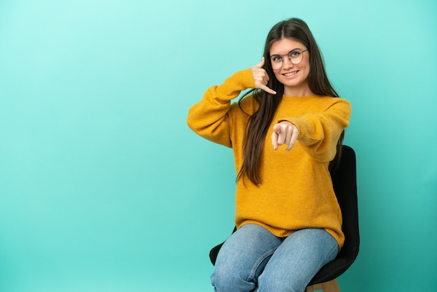 Young caucasian woman sitting on a chair isolated on blue background making phone gesture and pointing front