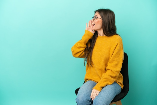 Young caucasian woman sitting on a chair isolated on blue background shouting with mouth wide open to the lateral