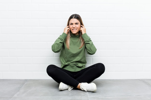 Young caucasian woman sitting on the floor covering ears with hands.
