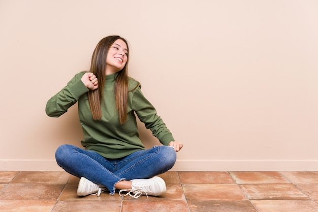 Young caucasian woman sitting on the floor isolated dancing and having fun.