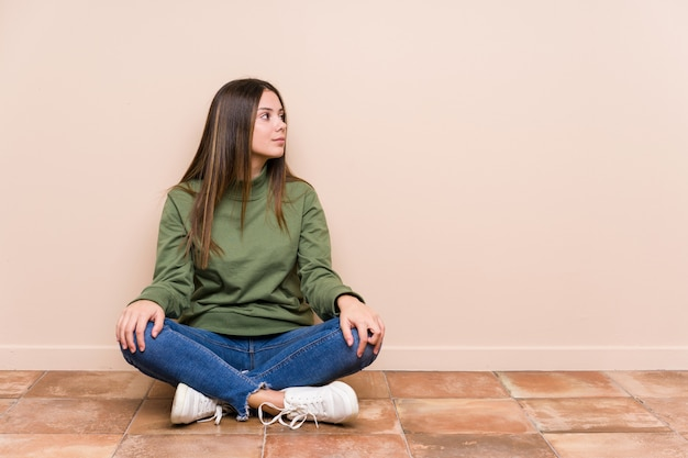Young caucasian woman sitting on the floor isolated gazing left, sideways pose.
