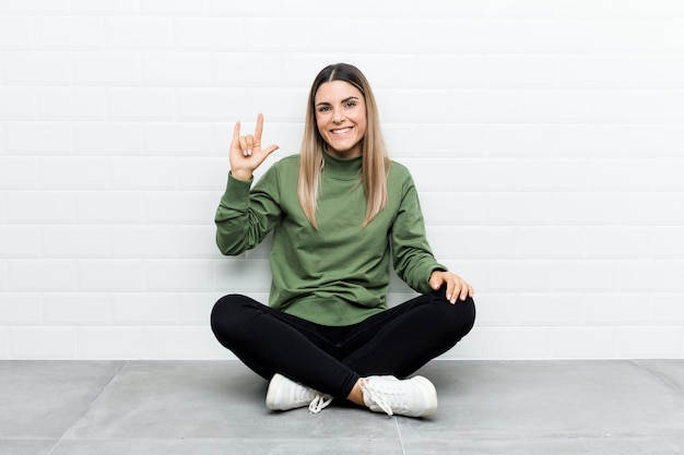 Young caucasian woman sitting on the floor showing a horns gesture as a revolution concept.