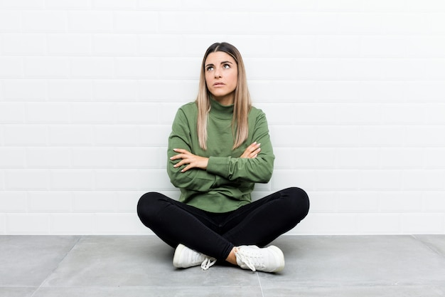 Young caucasian woman sitting on the floor tired of a repetitive task.
