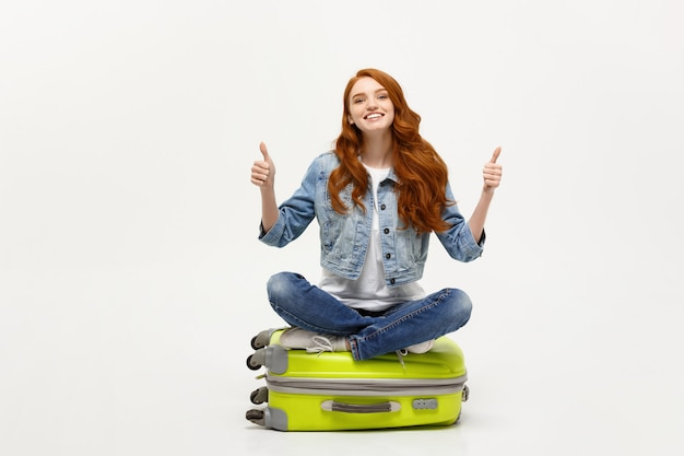 Young caucasian woman sitting on the luggage valise showing thumb up.