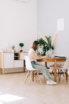 Молодая кавказская женщина, сидящая на стуле за кухонным столом у себя дома.