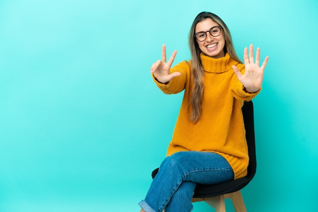 손가락으로 여덟 세 파란색 배경에 고립의 자에 앉아 젊은 백인 여자