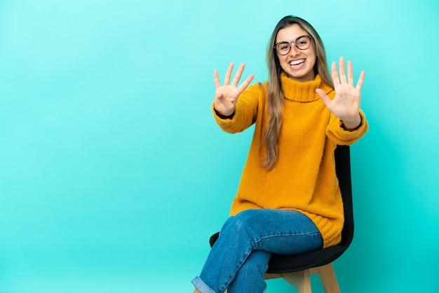 Молодая кавказская женщина сидит на стуле, изолированном на синем фоне, считая девять пальцами
