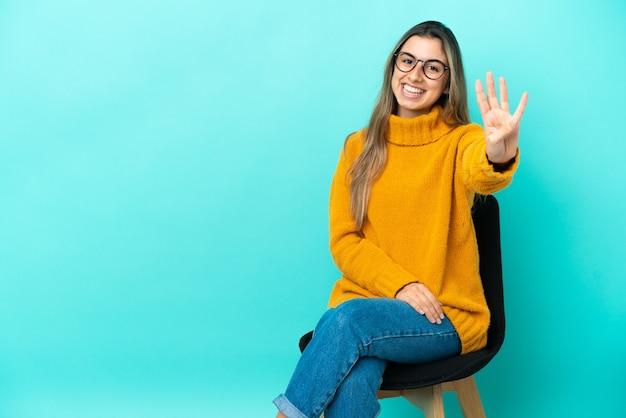 Молодая кавказская женщина сидит на стуле, изолированном на синем фоне, счастлива и считает четыре пальцами