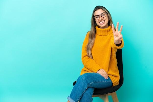 幸せな青い背景で隔離の椅子に座って、指で3を数える若い白人女性