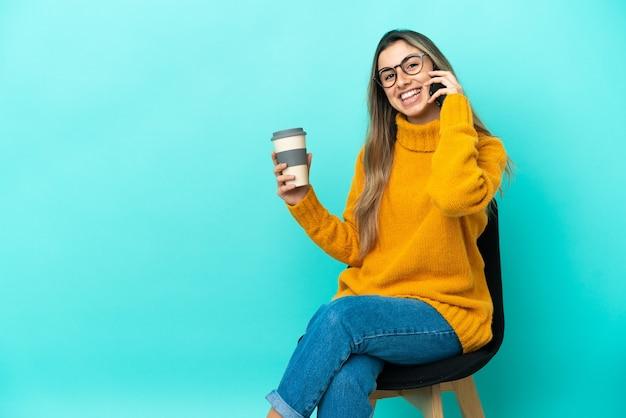 Молодая кавказская женщина сидит на стуле, изолированном на синем фоне, держит кофе на вынос и мобильный
