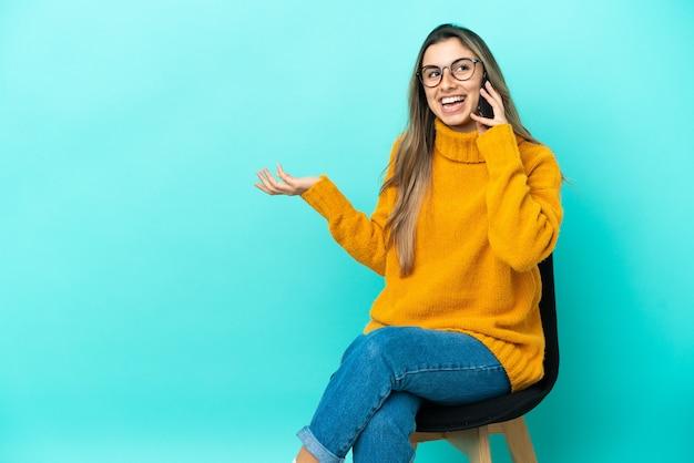 Молодая кавказская женщина сидит на стуле, изолированном на синем фоне, разговаривает с кем-то по мобильному телефону