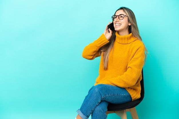 Молодая кавказская женщина сидит на стуле, изолированном на синем фоне, разговаривает по мобильному телефону